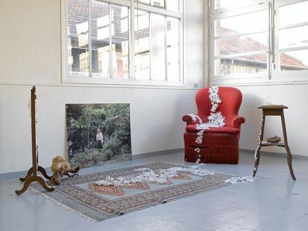 Simone • Fleurs en tissus, pâte à modeler, tapis, fauteuil, guéridon, fouine empaillée, nid et photographie numérique. 280 * 180 cm • 2009 • Vue de l'installation •Usine Chapal, Montreuil
